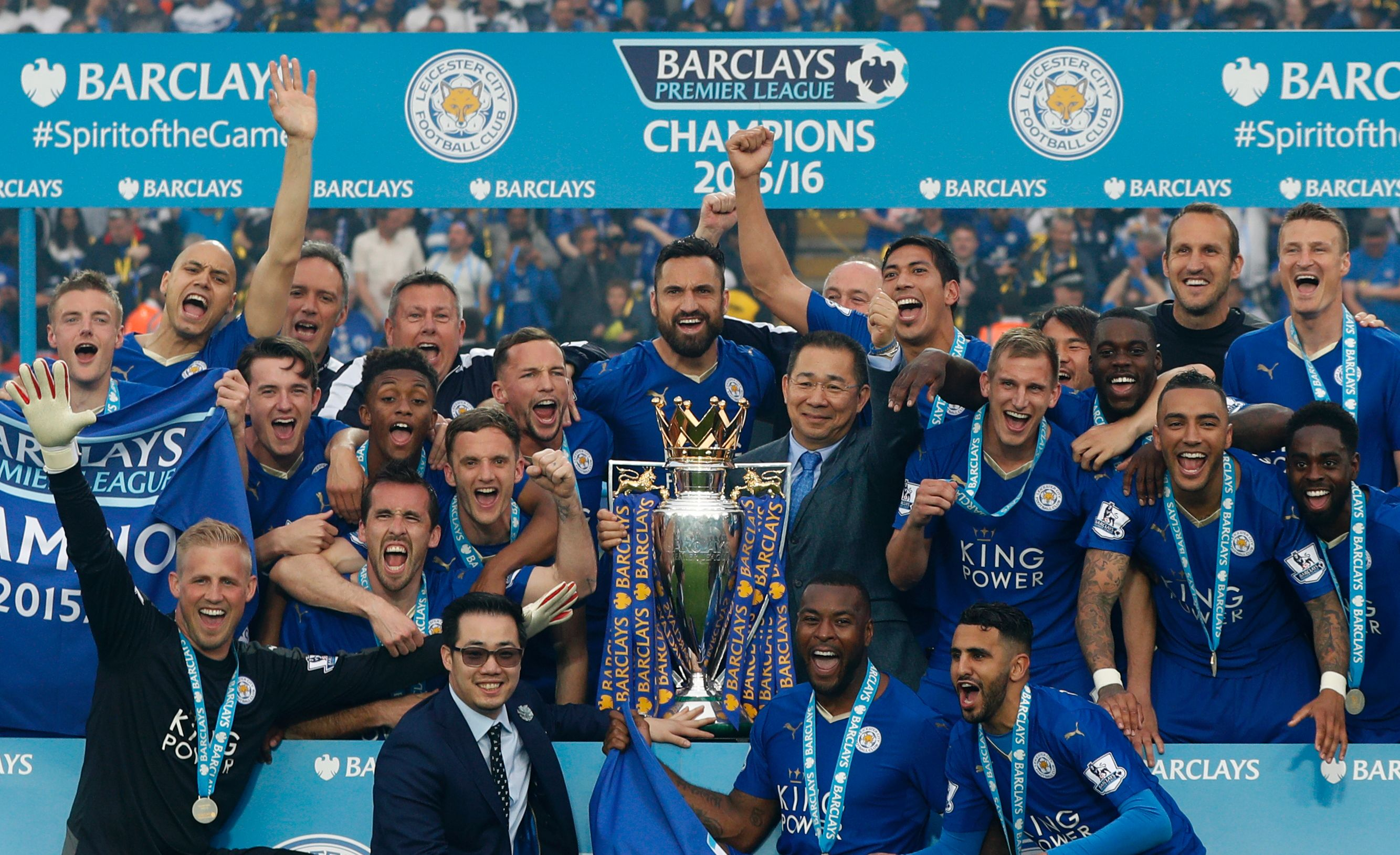 Leicester City players and Leicester City's Thai chairman Vichai Srivaddhanaprabha (C) pose with the Premier league trophy after winning the league and the English Premier League football match between Leicester City and Everton at King Power Stadium in Leicester, central England on May 7, 2016. / AFP / ADRIAN DENNIS / RESTRICTED TO EDITORIAL USE. No use with unauthorized audio, video, data, fixture lists, club/league logos or 'live' services. Online in-match use limited to 75 images, no video emulation. No use in betting, games or single club/league/player publications.  /         (Photo credit should read ADRIAN DENNIS/AFP/Getty Images)
