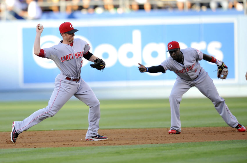July 27, 2013; Los Angeles, CA, USA; Cincinnati Reds shortstop Zack Cozart (2) throws to first after second baseman Brandon Phillips (4) tosses the ball to him during the second inning against the Los Angeles Dodgers at Dodger Stadium. Mandatory Credit: Gary A. Vasquez-USA TODAY Sports