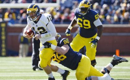 Apr 4, 2015; Ann Arbor, MI, USA; Michigan Wolverine quarterback Alex Malzone is tackled by defensive lineman Ryan Glasgow during the Spring football game at Michigan Stadium. Rick Osentoski-USA TODAY Sports