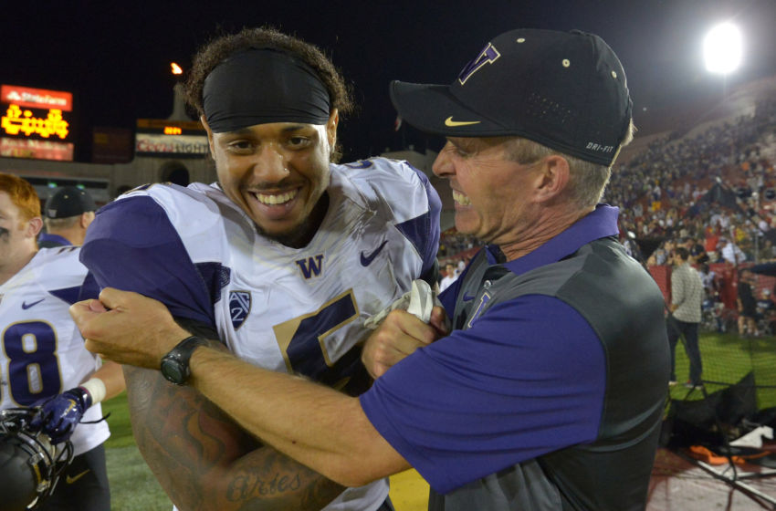 Oct 8, 2015; Los Angeles, CA, USA; Washington Huskies coach Chris Peterson (R) celebrates with defensive end Joe Mathis (5) after defeating the Southern California Trojans 17-12 at Los Angeles Memorial Coliseum. Mandatory Credit: Kirby Lee-USA TODAY Sports