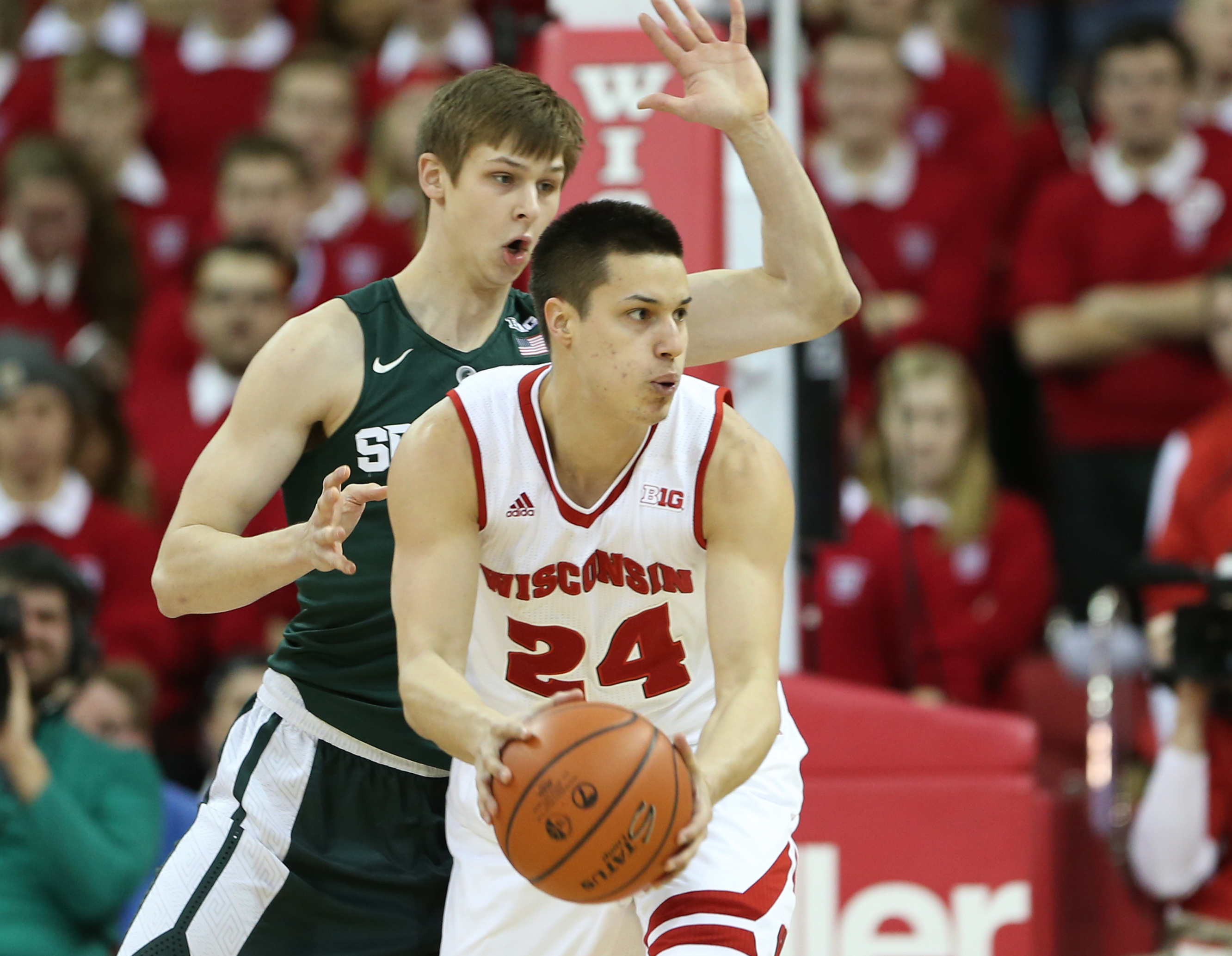 Jan 17, 2016; Madison, WI, USA; Wisconsin Badgers guard Bronson Koenig (24) looks to pass as Michigan State Spartans guard Matt McQuaid (20) defends. Wisconsin defeated Michigan State 77-76 at the Kohl Center. Mandatory Credit: Mary Langenfeld-USA TODAY Sports