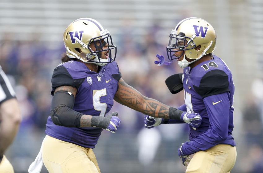 Sep 3, 2016; Seattle, WA, USA; Washington Huskies linebacker Joe Mathis (5) celebrates a tackle with defensive back Jojo McIntosh (14) against the Rutgers Scarlet Knights during the first quarter at Husky Stadium. Washington won 48-13. Mandatory Credit: Jennifer Buchanan-USA TODAY Sports