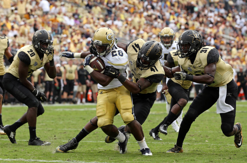 Sep 17, 2016; Atlanta, GA, USA; Georgia Tech Yellow Jackets running back Dedrick Mills (26) scores a rushing touchdown against Vanderbilt Commodores linebacker Zach Cunningham (41) and cornerback Tre Herndon (31) in the third quarter of their game at Bobby Dodd Stadium. The Yellow Jackets won 38-7. Mandatory Credit: Jason Getz-USA TODAY Sports