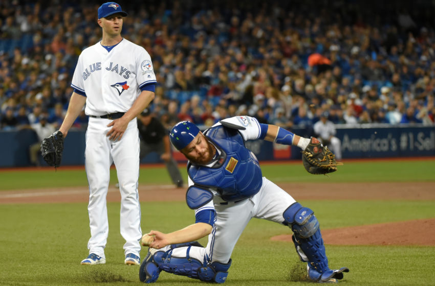 Sep 26, 2016; Toronto, Ontario, CAN; Toronto Blue Jays starting pitcher J.A. Happ (33) watches as catcher Russell Martin (55) makes a throwing error on a ball hit by New York Yankees Brett Gardner (not pictured) in the first inning at Rogers Centre. Mandatory Credit: Dan Hamilton-USA TODAY Sports