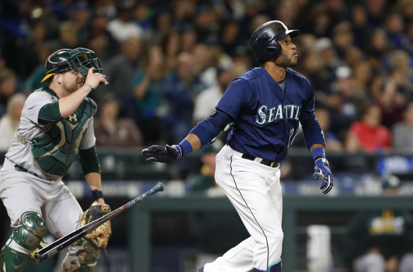 Oct 1, 2016; Seattle, WA, USA; Seattle Mariners second baseman Robinson Cano (22) drops his bat as he watches his two-run home run leave the park as Oakland Athletics catcher Stephen Vogt (21) looks on during the fifth inning at Safeco Field. Mandatory Credit: Jennifer Buchanan-USA TODAY Sports
