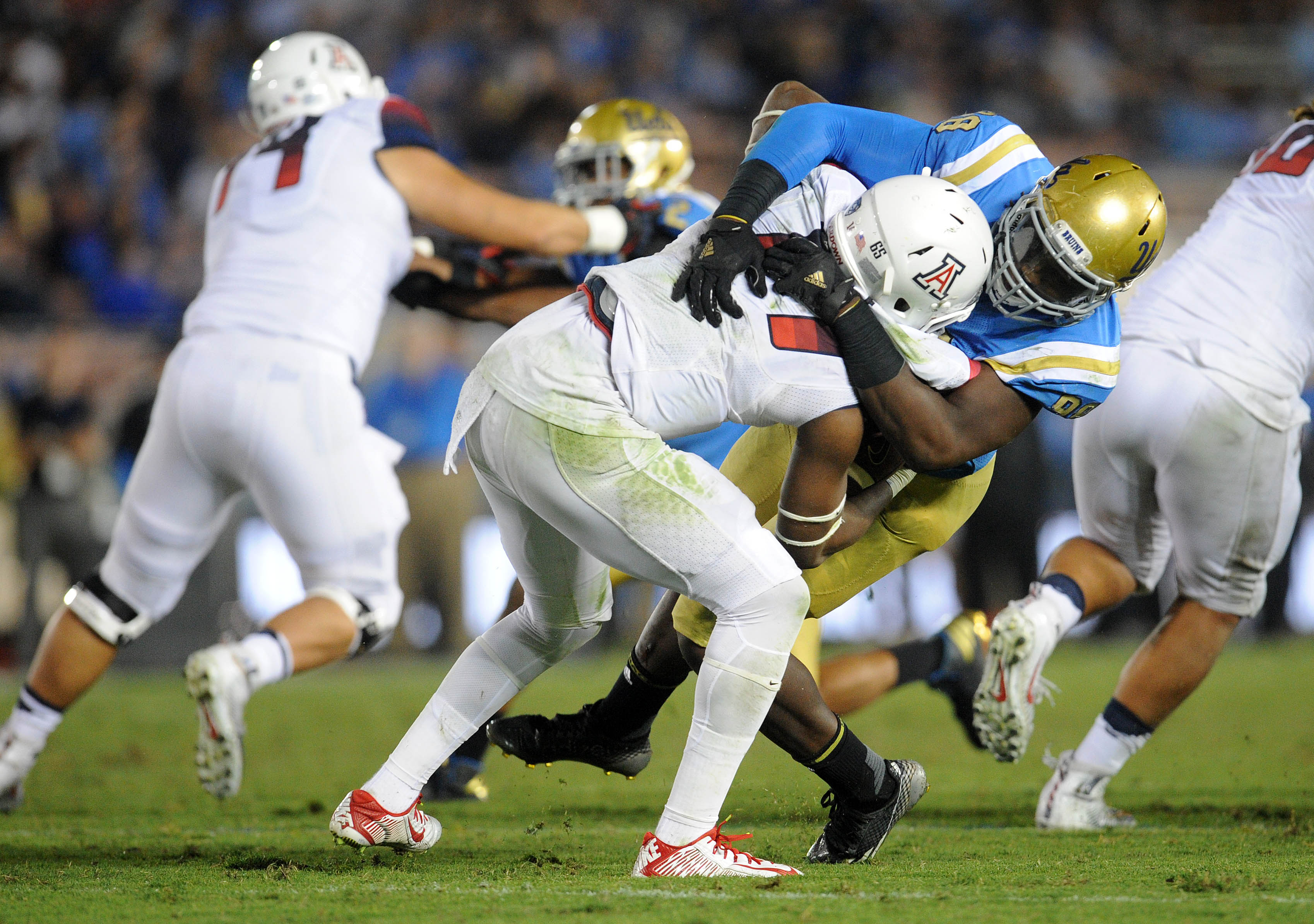 October 1, 2016; Pasadena, CA, USA; UCLA Bruins defensive lineman Takkarist McKinley (98) brings down Arizona Wildcats quarterback Khalil Tate (14) during the second half at Rose Bowl. Mandatory Credit: Gary A. Vasquez-USA TODAY Sports