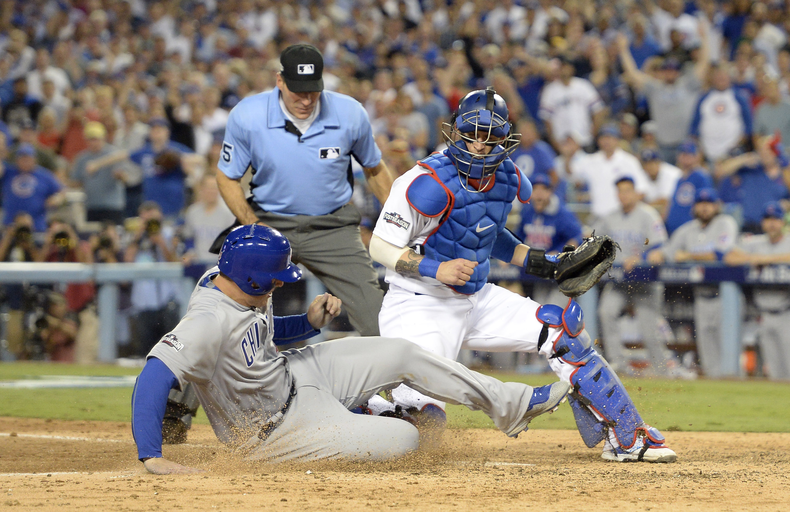Oct 19, 2016; Los Angeles, CA, USA; Chicago Cubs first baseman Anthony Rizzo (44) scores a run past Los Angeles Dodgers catcher Yasmani Grandal (9)  in the 6th inning during game four of the 2016 NLCS playoff baseball series at Dodger Stadium. Mandatory Credit: Richard Mackson-USA TODAY Sports