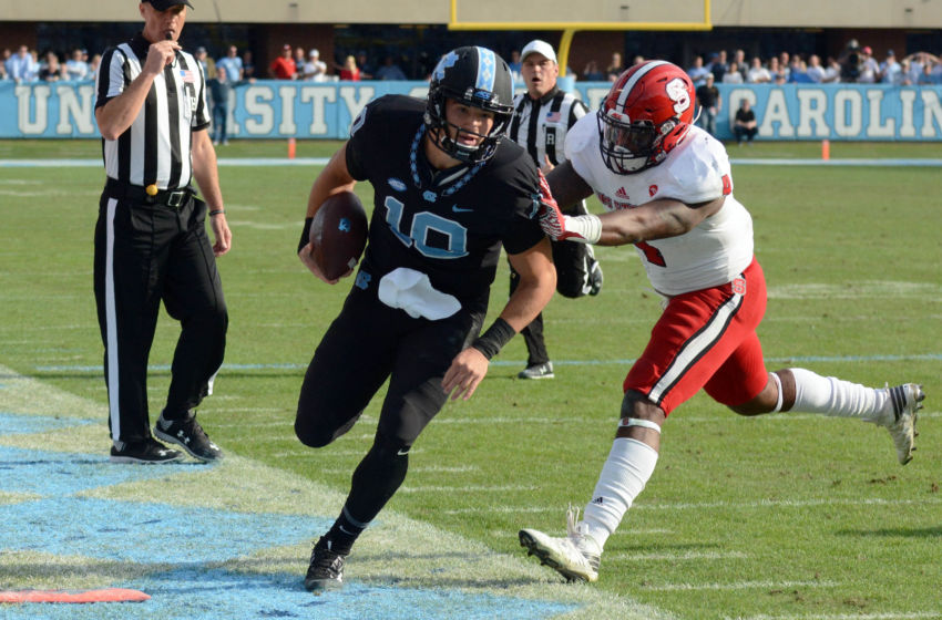 Nov 25, 2016; Chapel Hill, NC, USA; North Carolina Tar Heels quarterback Mitch Trubisky (10) is pushed out of bounds by North Carolina State Wolfpack linebacker Jarod Fernandez (4) during the second half at Kenan Memorial Stadium. The Wolfpack won 28-21. Mandatory Credit: Rob Kinnan-USA TODAY Sports