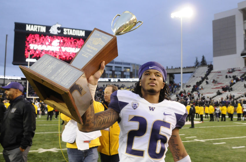 Nov 25, 2016; Pullman, WA, USA; Washington Huskies defensive back Sidney Jones (26) carries the the Apple Cup Trophy after a game against the Washington State Cougars after a game at Martin Stadium. The Huskies won 45-17. Mandatory Credit: James Snook-USA TODAY Sports