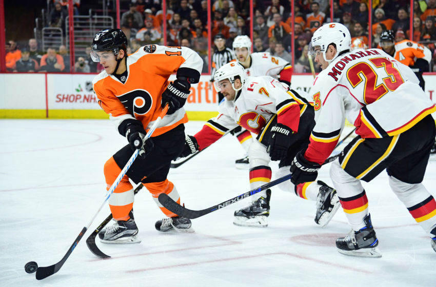 Nov 27, 2016; Philadelphia, PA, USA; Philadelphia Flyers center Travis Konecny (11) carries the puck against defenseman TJ Brodie (7) and Calgary Flames center Sean Monahan (23) during the second period at Wells Fargo Center. Mandatory Credit: Eric Hartline-USA TODAY Sports