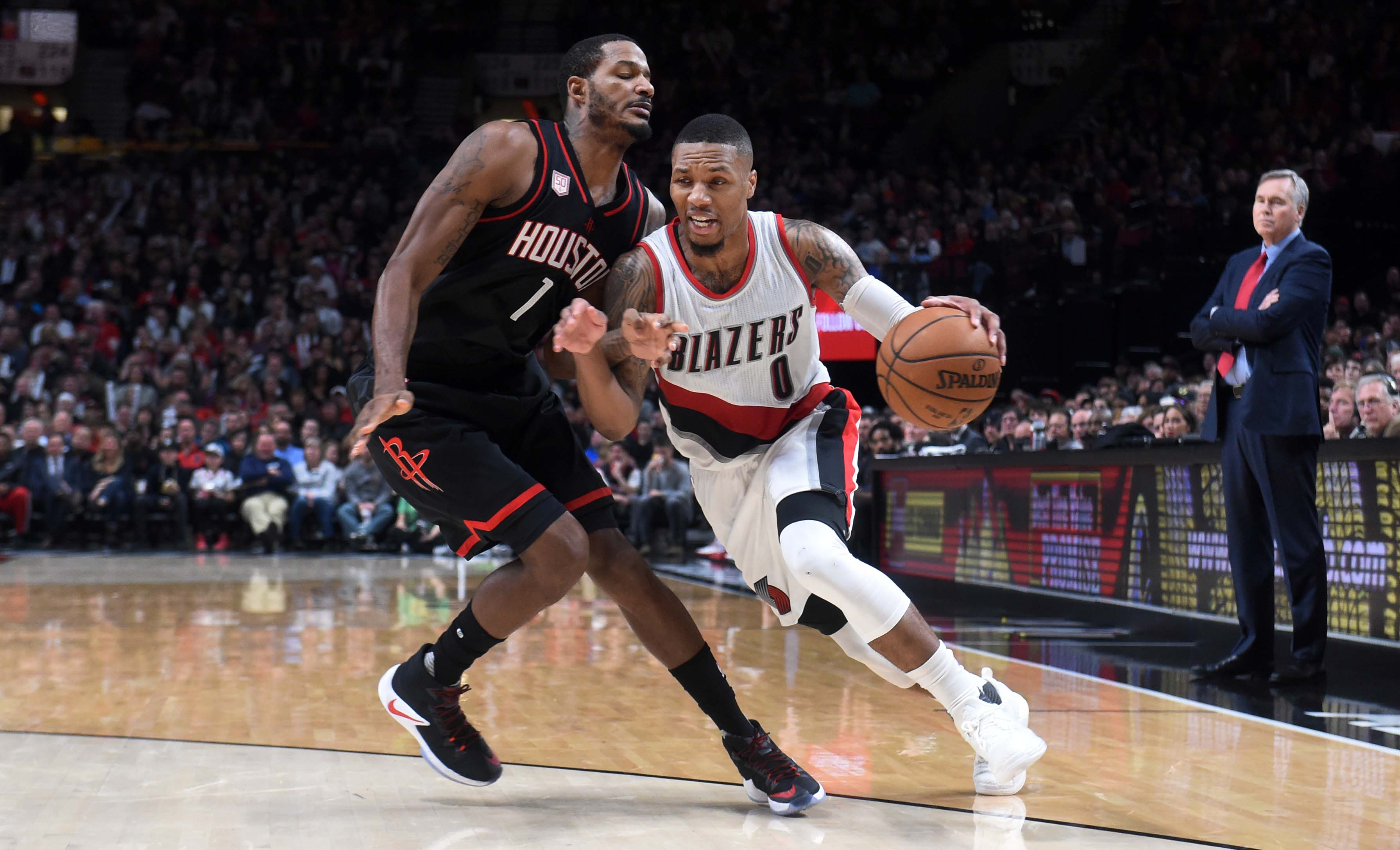 Nov 27, 2016; Portland, OR, USA; Portland Trail Blazers guard Damian Lillard (0) drives to the basket on Houston Rockets forward Trevor Ariza (1) during the fourth quarter of the game at the Moda Center at the Rose Quarter. The Rockets won 130-114. Mandatory Credit: Steve Dykes-USA TODAY Sports
