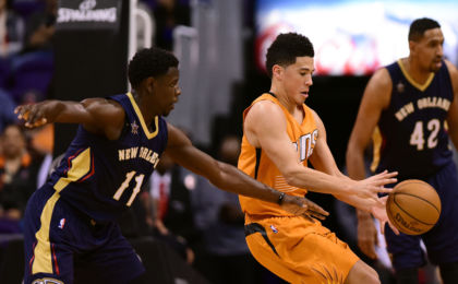 Dec 11, 2016; Phoenix, AZ, USA; Phoenix Suns guard Devin Booker (1) reaches for the ball in front of New Orleans Pelicans guard Jrue Holiday (11) in the first half at Talking Stick Resort Arena. The New Orleans Pelicans won 120 - 119 in overtime. Mandatory Credit: Jennifer Stewart-USA TODAY Sports