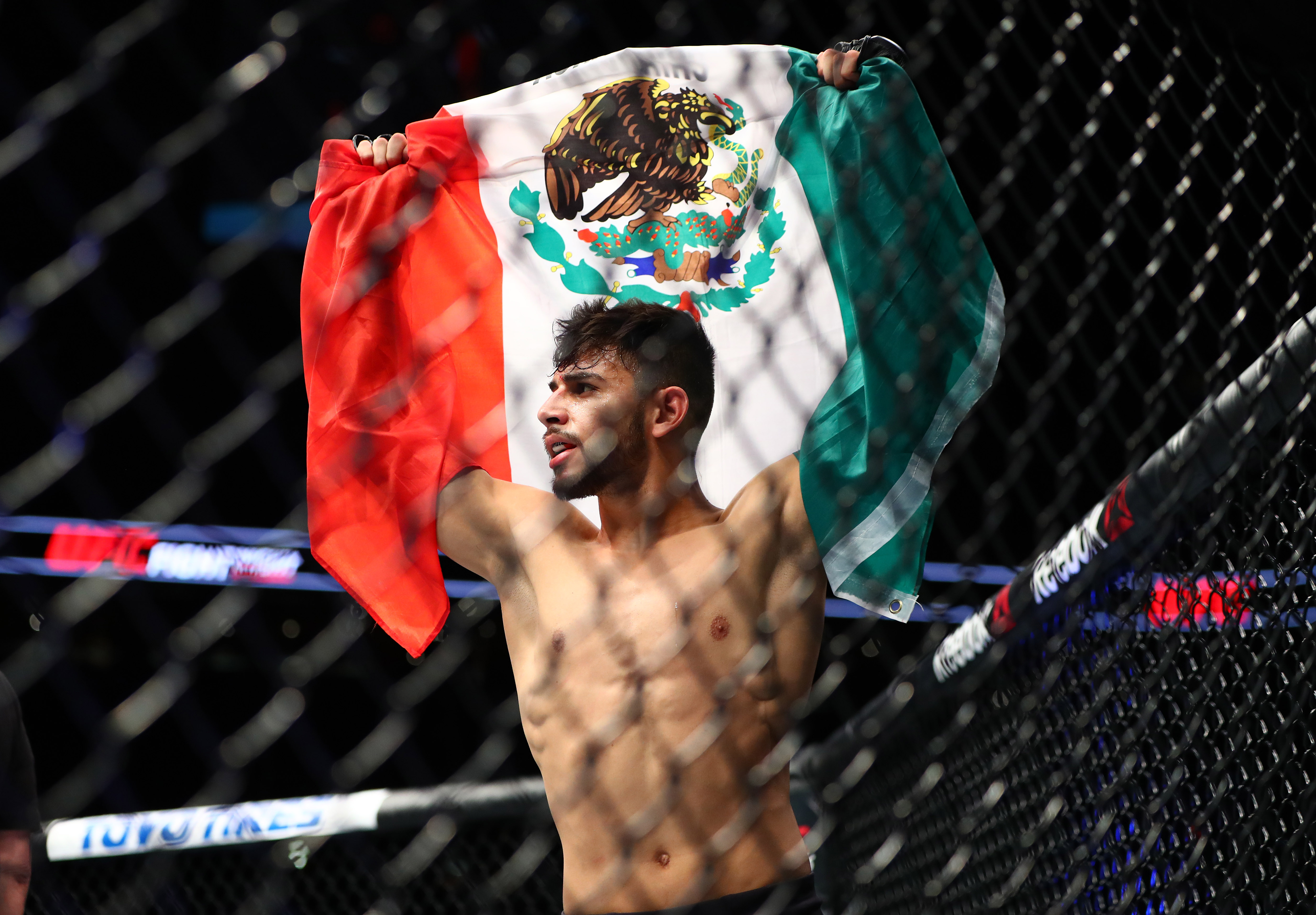 Jan 15, 2017; Phoenix, AZ, USA; Yair Rodriguez holds a Mexico flag as he celebrates his TKO of B.J. Penn (not pictured) during UFC Fight Night at Talking Stick Resort Arena. Mandatory Credit: Mark J. Rebilas-USA TODAY Sports