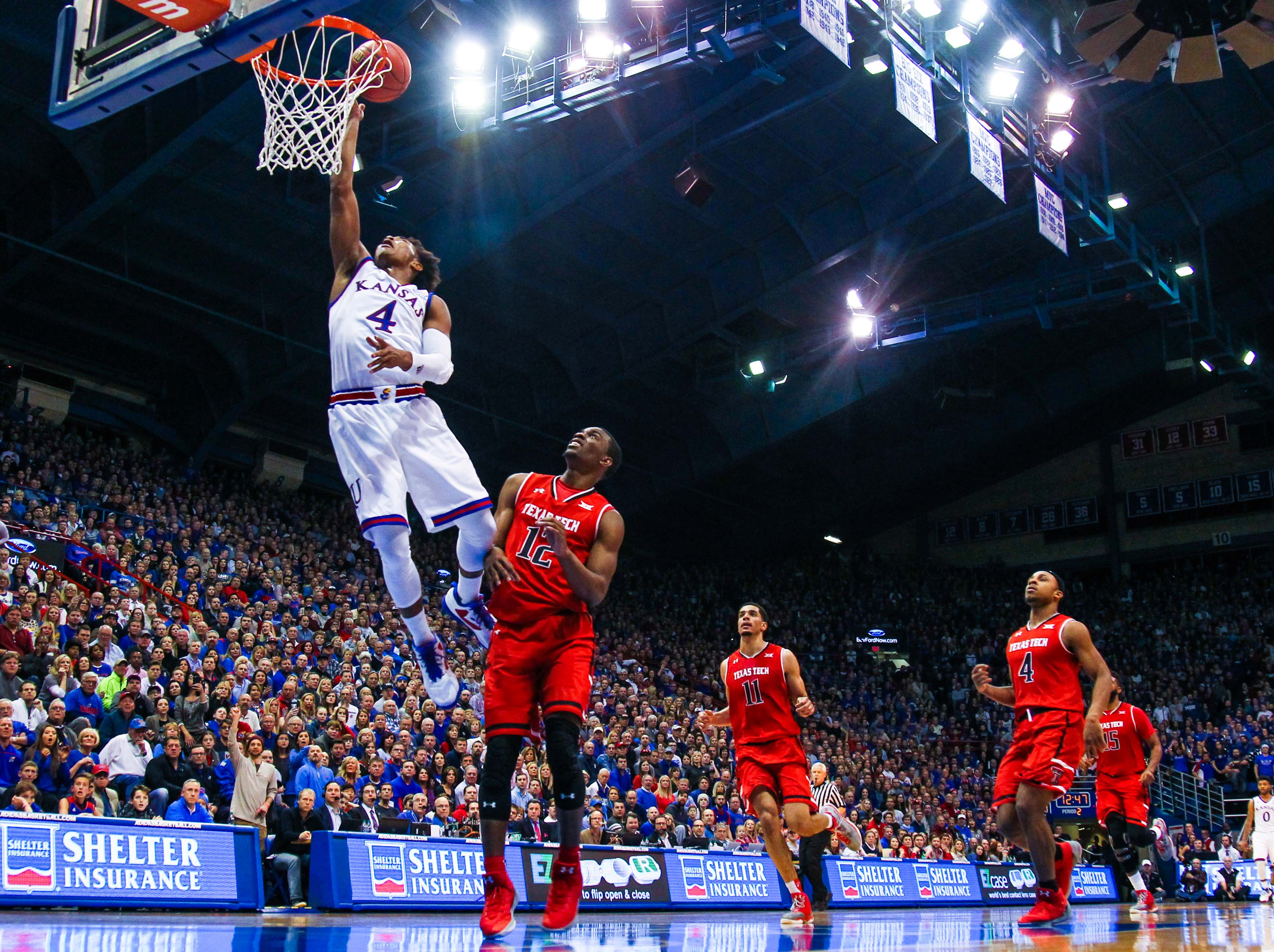 Jan 7, 2017; Lawrence, KS, USA;  Kansas Jayhawks guard Devonte' Graham (4) shoots a lay up as Texas Tech Red Raiders guard Keenan Evans (12) defends during the second half at Allen Fieldhouse. The Jayhawks won 85-68. Mandatory Credit: Jay Biggerstaff-USA TODAY Sports