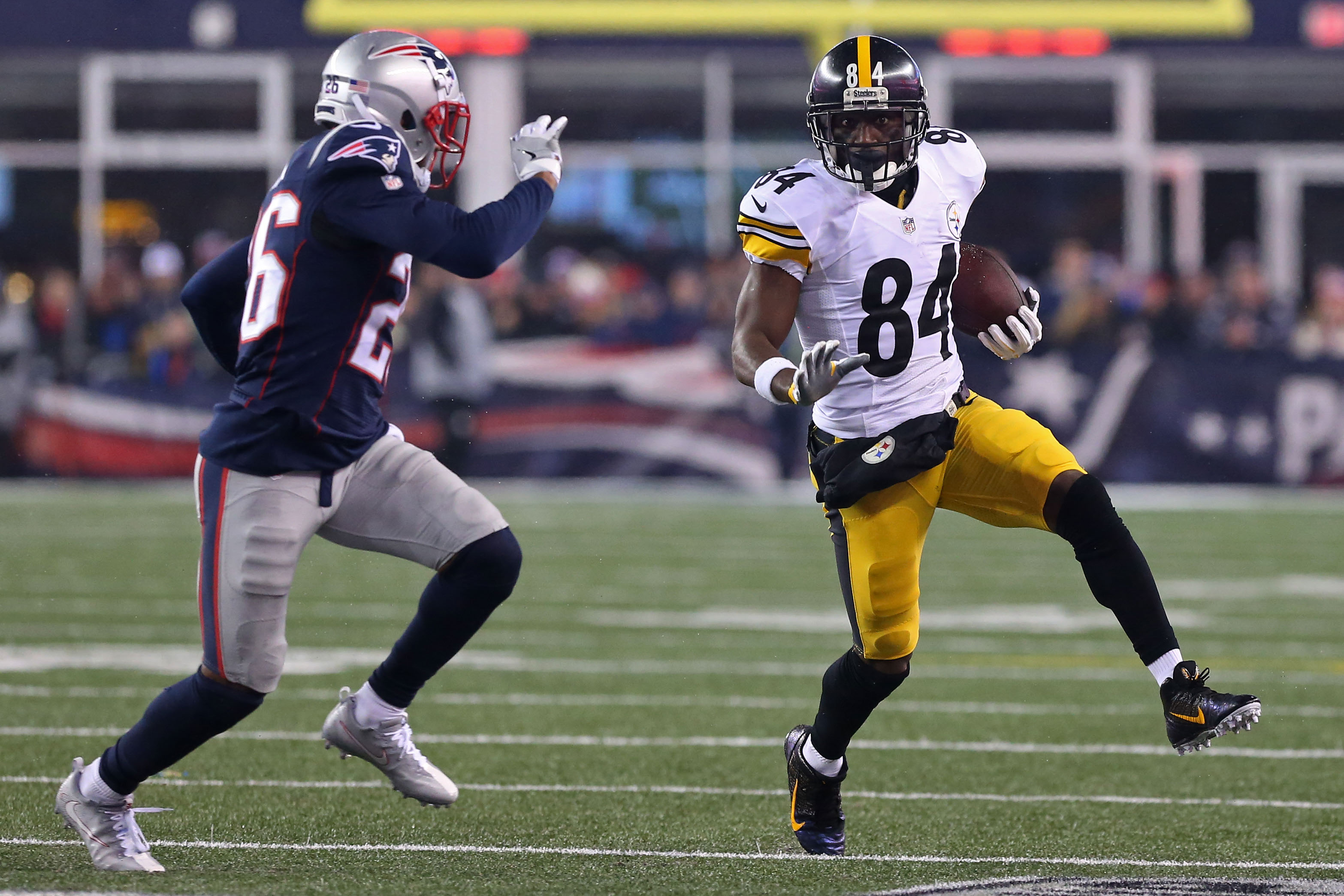 Jan 22, 2017; Foxborough, MA, USA; Pittsburgh Steelers wide receiver Antonio Brown (84) runs with the ball as New England Patriots cornerback Logan Ryan (26) chases in the 2017 AFC Championship Game at Gillette Stadium. Mandatory Credit: Geoff Burke-USA TODAY Sports
