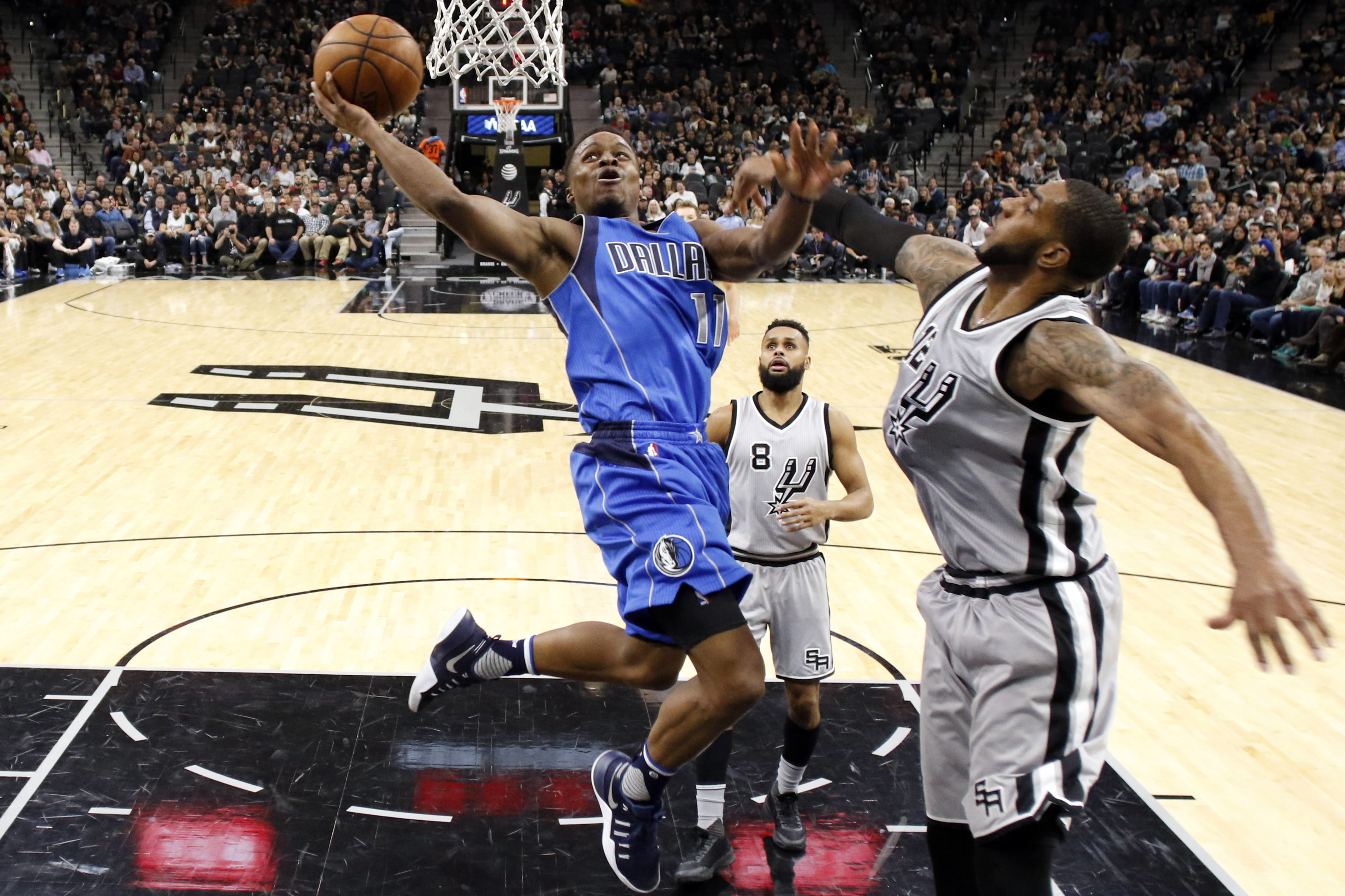 Jan 29, 2017; San Antonio, TX, USA; Dallas Mavericks guard Yogi Ferrell (11) shoots the ball past San Antonio Spurs power forward LaMarcus Aldridge (12) during the second half at AT&T Center. Mavericks won 105-101. Mandatory Credit: Soobum Im-USA TODAY Sports