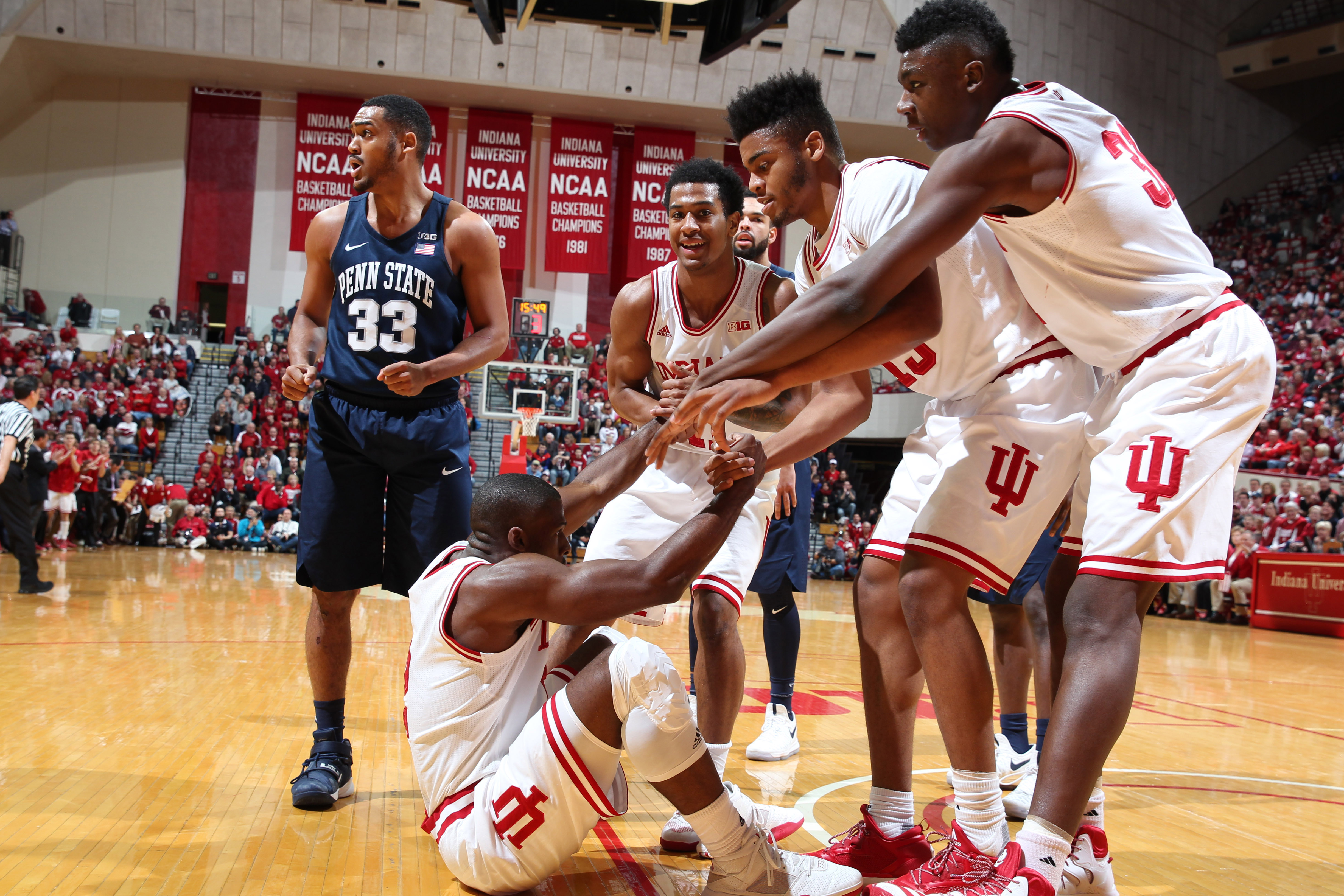 Feb 1, 2017; Bloomington, IN, USA; Indiana Hoosiers guard Josh Newkirk (2) gets helped up off the floor from center Thomas Bryant (31) and forward Juwan Morgan (13) against the Penn State Nittany Lions at Assembly Hall. Mandatory Credit: Brian Spurlock-USA TODAY Sports
