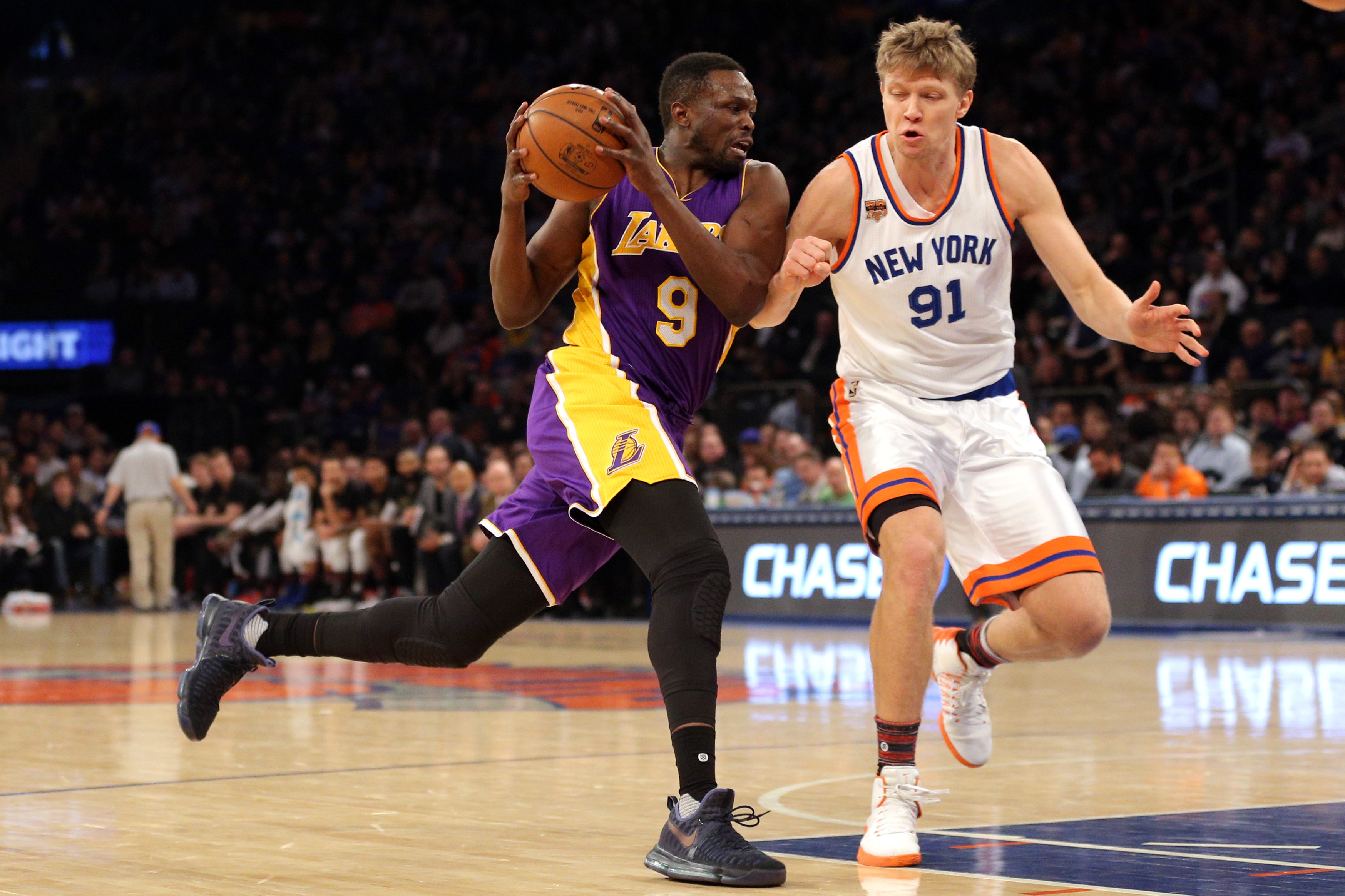 Feb 6, 2017; New York, NY, USA; Los Angeles Lakers small forward Luol Deng (9) drives against New York Knicks small forward Mindaugas Kuzminskas (91) during the second quarter at Madison Square Garden. Mandatory Credit: Brad Penner-USA TODAY Sports