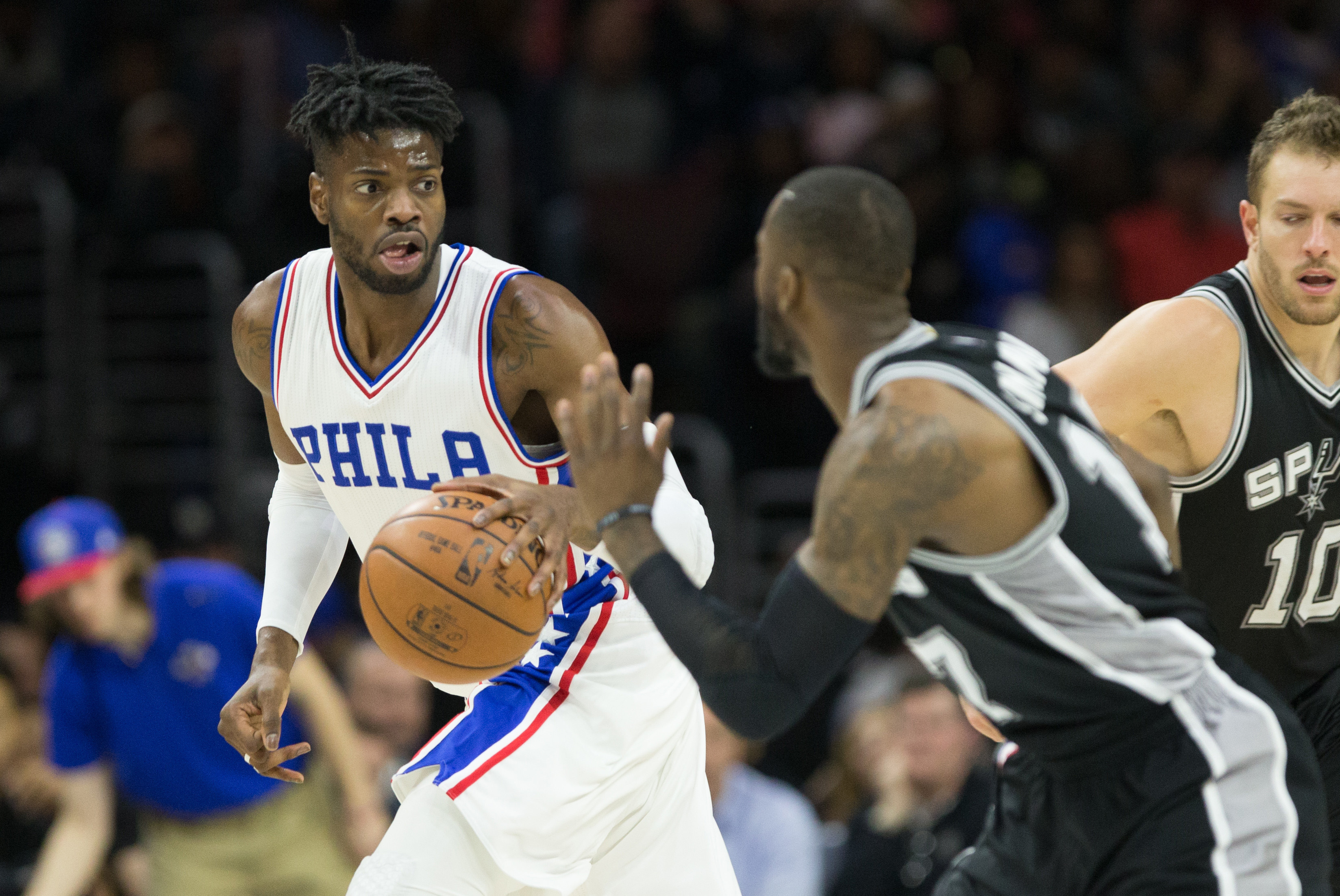 Feb 8, 2017; Philadelphia, PA, USA; Philadelphia 76ers forward Nerlens Noel (4) dribbles past San Antonio Spurs guard Jonathon Simmons (17) during the third quarter at Wells Fargo Center. The San Antonio Spurs won 111-103. Mandatory Credit: Bill Streicher-USA TODAY Sports