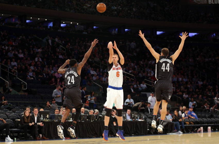 Nov 9, 2016; New York, NY, USA; New York Knicks power forward Kristaps Porzingis (6) shoots a three point shot over Brooklyn Nets shooting guard Rondae Hollis-Jefferson (24) and Brooklyn Nets shooting guard Bojan Bogdanovic (44) during the third quarter at Madison Square Garden. Mandatory Credit: Brad Penner-USA TODAY Sports