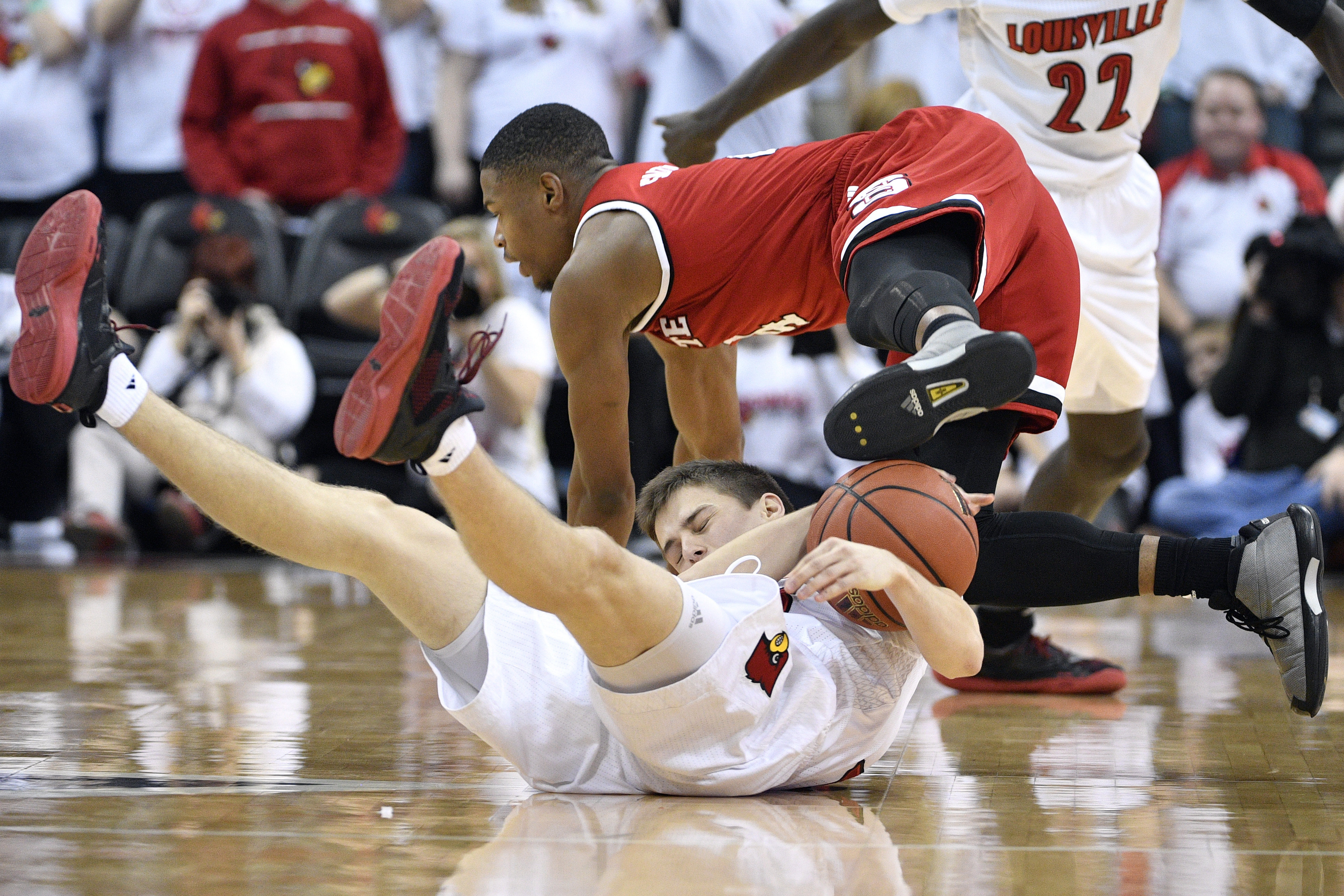 Jan 29, 2017; Louisville, KY, USA; North Carolina State Wolfpack guard Dennis Smith Jr. (4) falls over Louisville Cardinals guard David Levitch (23) while scrambling for the ball during the second half at KFC Yum! Center. Louisville defeated North Carolina State 85-60. Mandatory Credit: Jamie Rhodes-USA TODAY Sports