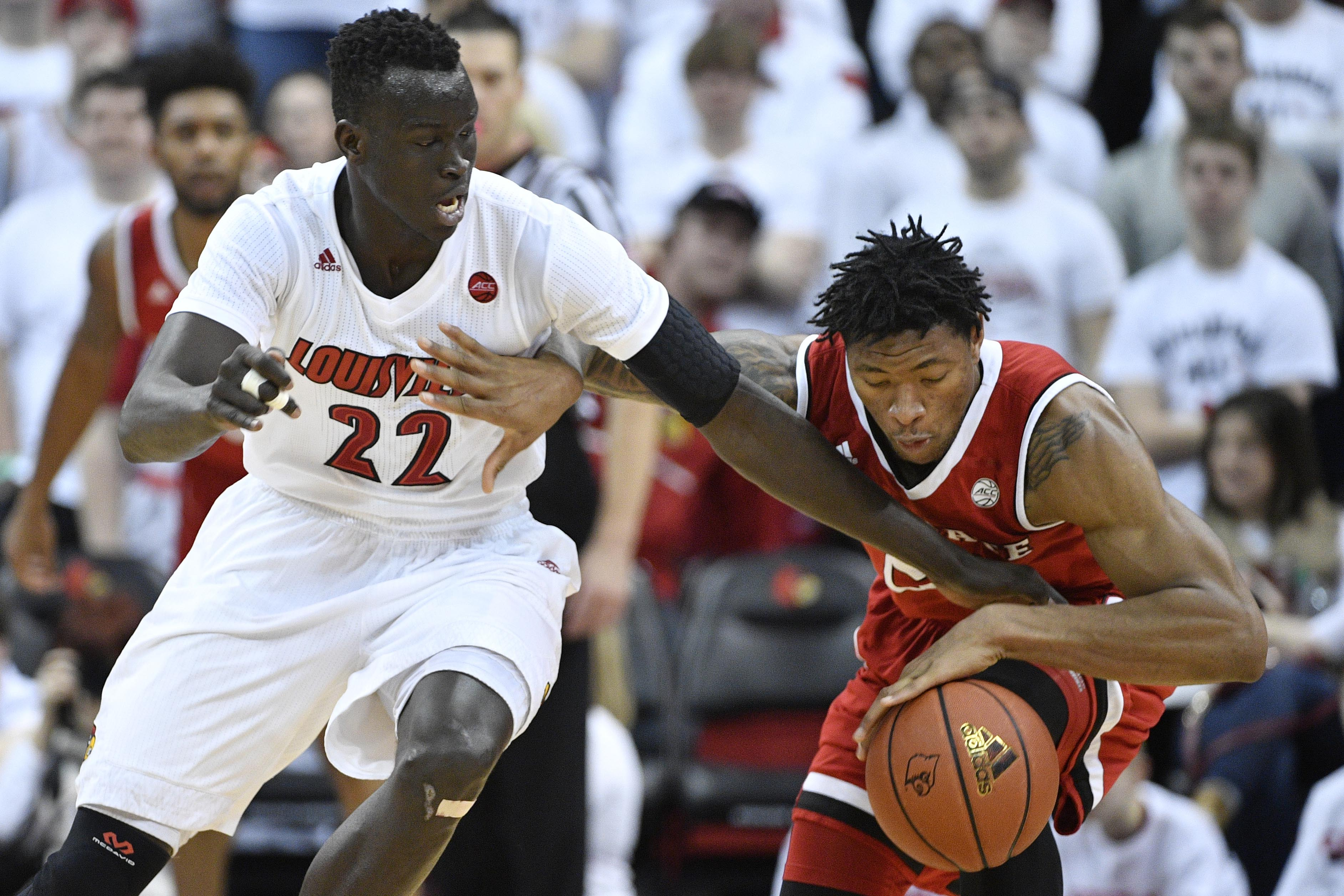 Jan 29, 2017; Louisville, KY, USA; Louisville Cardinals forward Deng Adel (22) tries to steal the ball from North Carolina State Wolfpack forward Ted Kapita (23) during the second half at KFC Yum! Center. The Cardinals won 85-60. Mandatory Credit: Jamie Rhodes-USA TODAY Sports