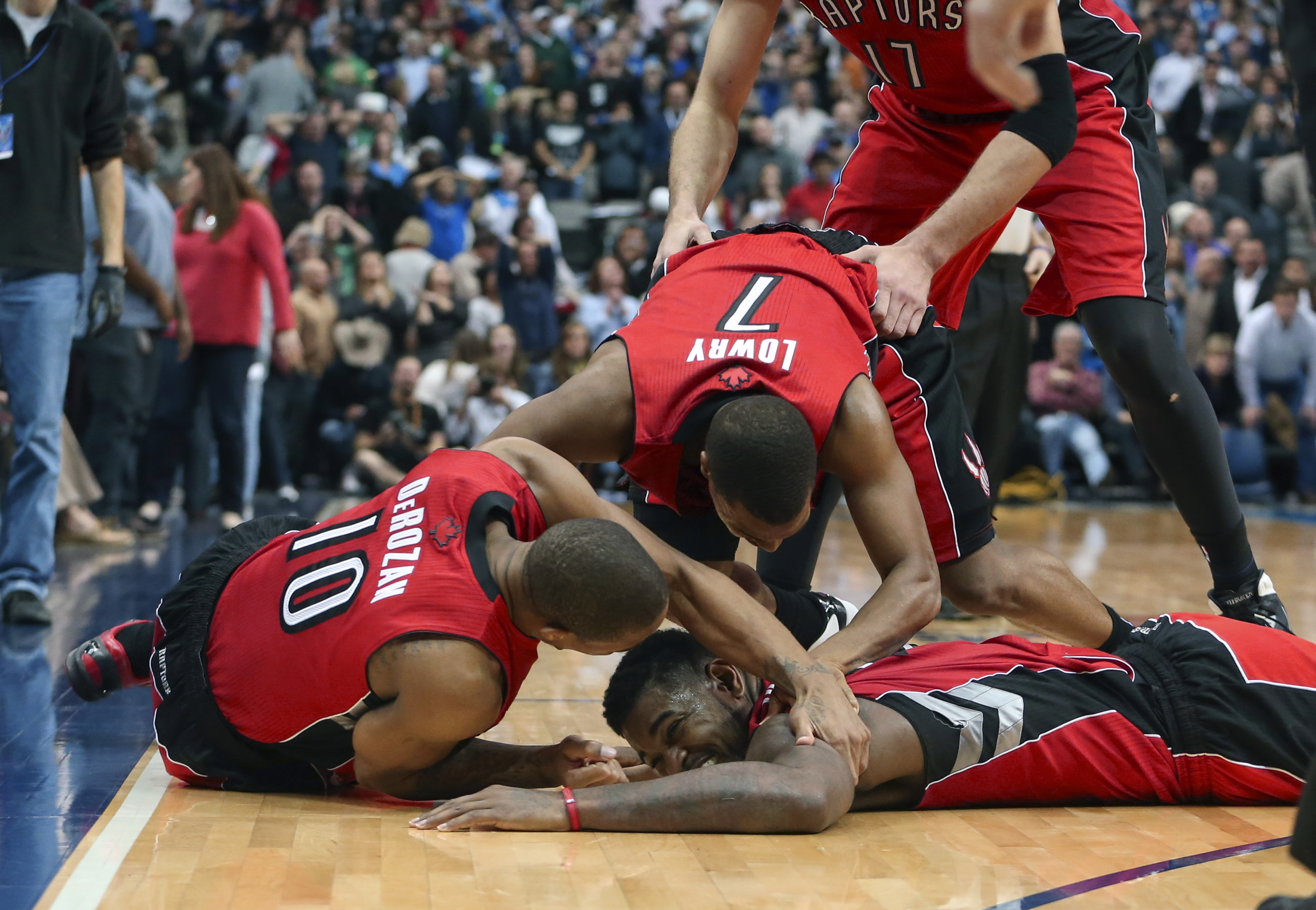 Dec 20, 2013; Dallas, TX, USA; Toronto Raptors power forward Amir Johnson (bottom) celebrates with point guard Kyle Lowry (7) and shooting guard DeMar DeRozan (10) after defeating the Dallas Mavericks in overtime at American Airlines Center. Mandatory Credit: Kevin Jairaj-USA TODAY Sports