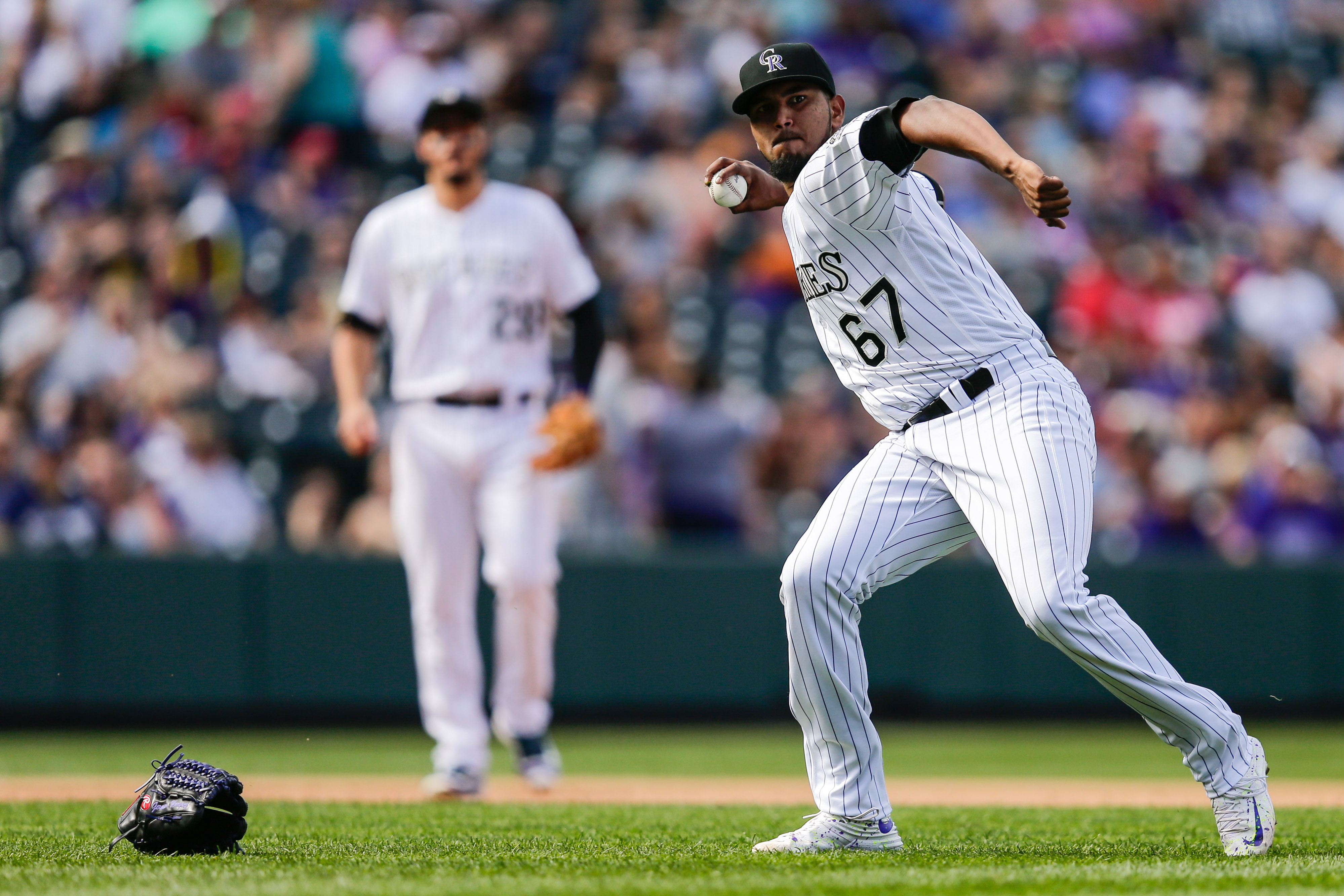 Oct 2, 2016; Denver, CO, USA; Colorado Rockies starting pitcher German Marquez (67) throws to first after losing his glove fielding the ball in the fourth inning against the Milwaukee Brewers at Coors Field. Mandatory Credit: Isaiah J. Downing-USA TODAY Sports