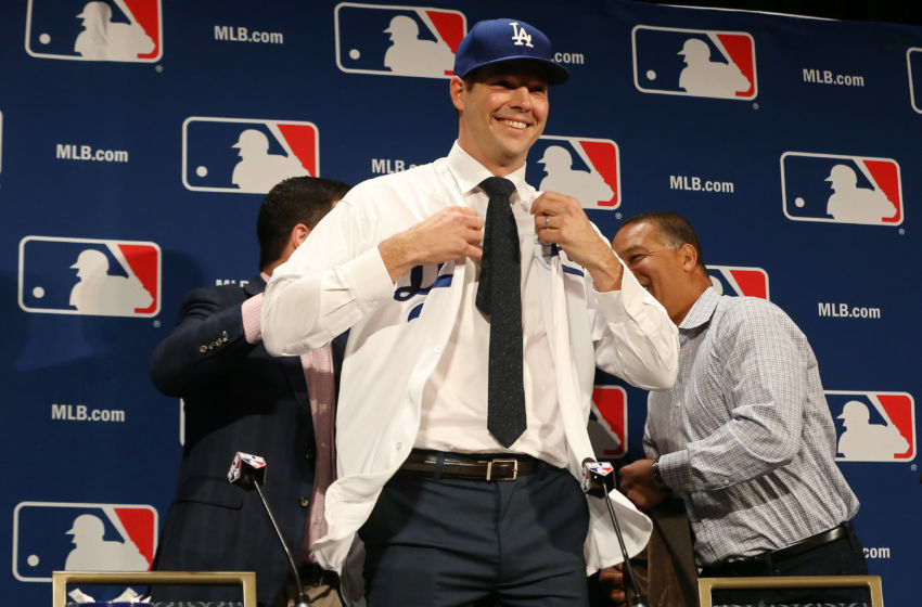 Dec 5, 2016; National Harbor, MD, USA; Los Angeles Dodgers pitcher Rich Hill puts on a Dodgers jersey at a press conference announcing Hill's signing a three year contract during the 2016 MLB Winter Meetings at Gaylord National Resort & Convention Center. Mandatory Credit: Geoff Burke-USA TODAY Sports