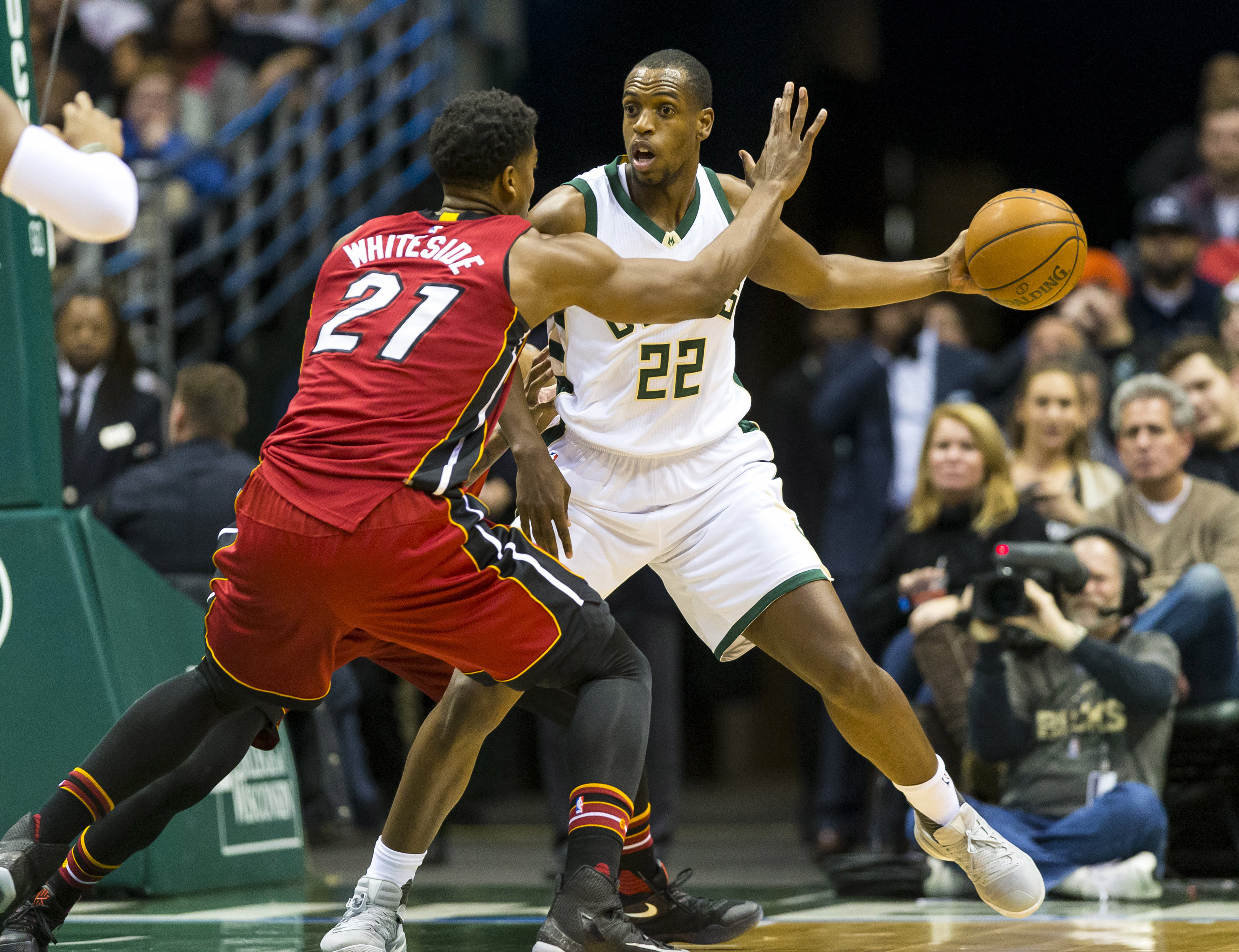 Feb 8, 2017; Milwaukee, WI, USA; Milwaukee Bucks guard Khris Middleton (22) passes the ball around Miami Heat center Hassan Whiteside (21) during the first quarter at BMO Harris Bradley Center. Mandatory Credit: Jeff Hanisch-USA TODAY Sports